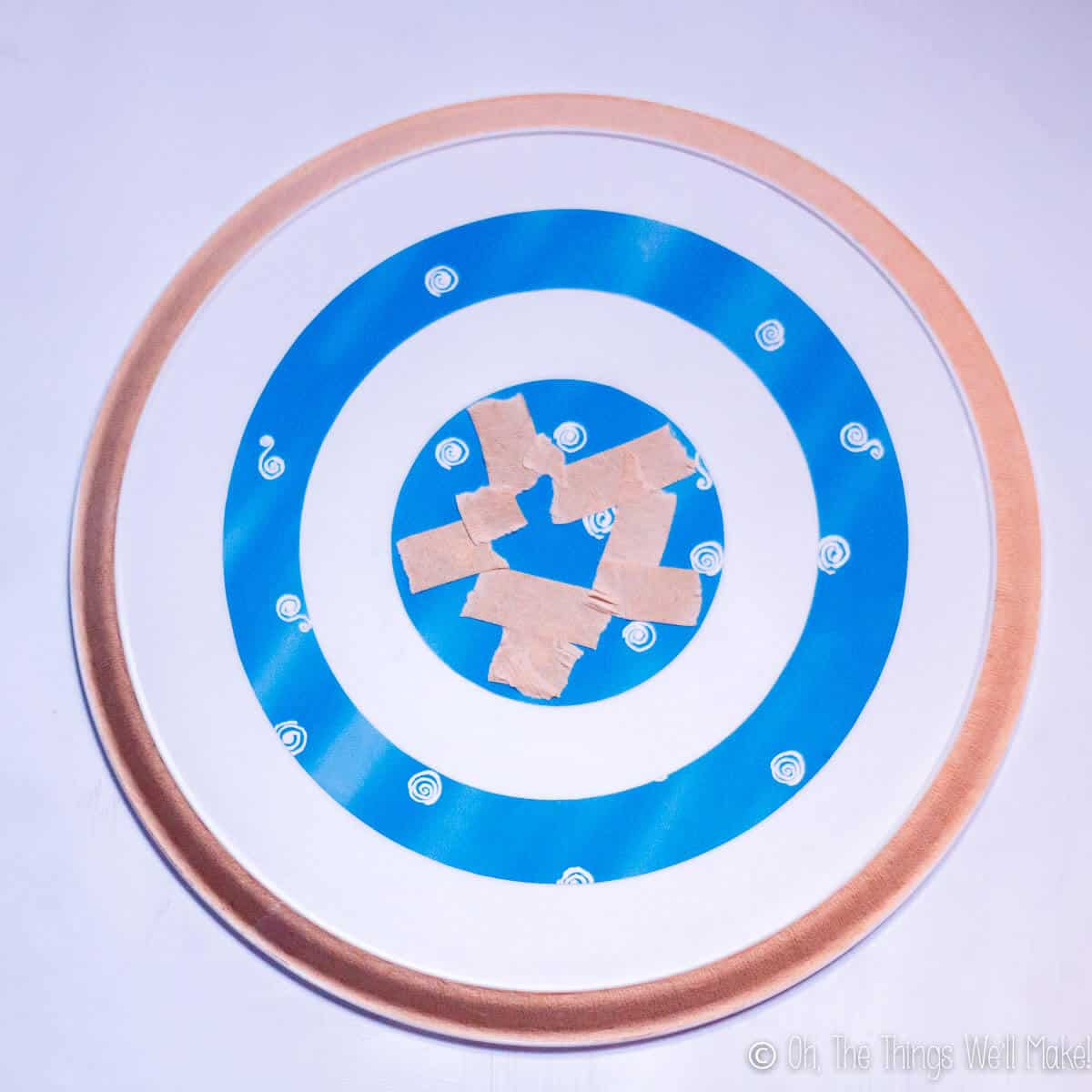 Taping off sections of a plastic tray before painting it to make it into a Captain America shield.