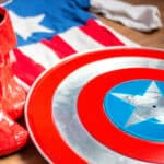 A homemade Captain America shield next to homemade boots and homemade costume