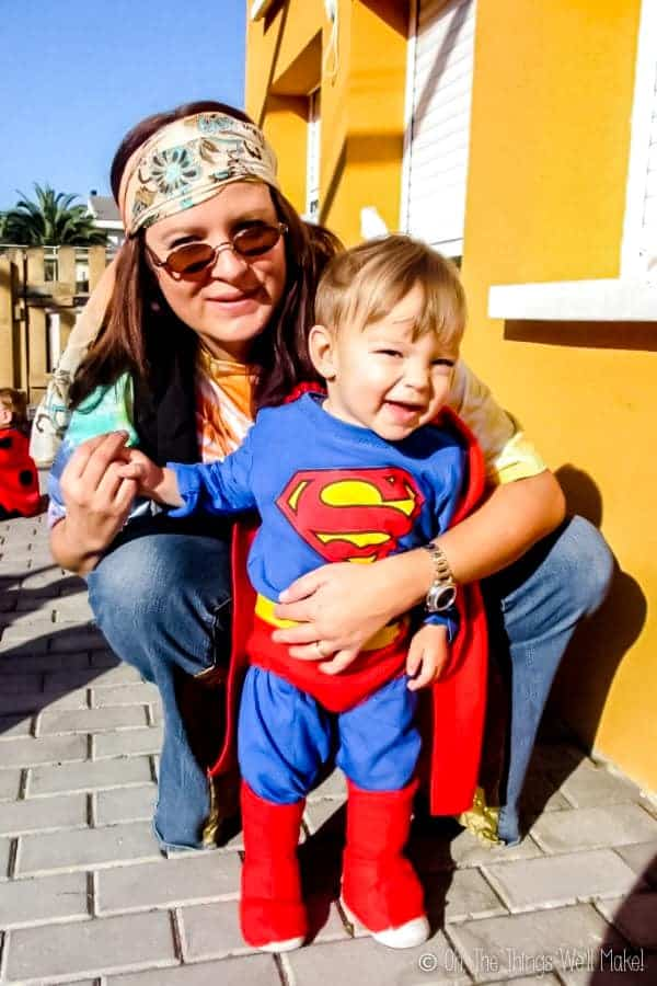A boy, wearing a homemade Superman costume, with his mother, wearing a hippy costume