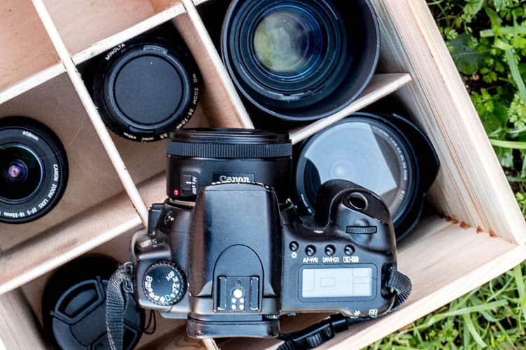 A camera sitting on top of a wooden box filled with different objective lenses