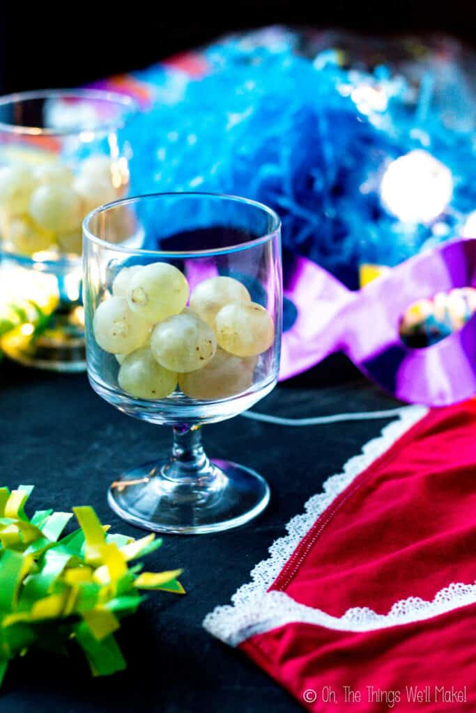 a glass filled with 12 lucky grapes next to red underwear, a mask, and other cotillion party favors.