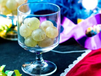 Twelve grapes in a glass next to red underwear and party favors, ready for celebrating New Year's in Spain.