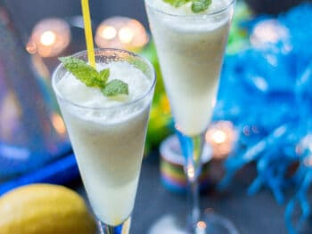 Two champagne glasses filled with a lemon champagne sorbet and garnished with fresh spearmint leaves.