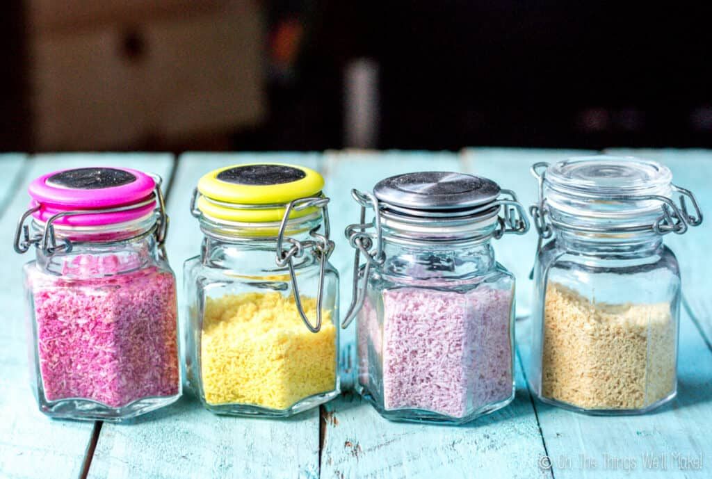 4 glass jars filled with 4 different types of colorful sprinkles made from shredded coconut after stored for 10 months. The colors have faded, but are still visible. From left to right: bright pink, yellow, purple, and what was once green, but is now more beige.