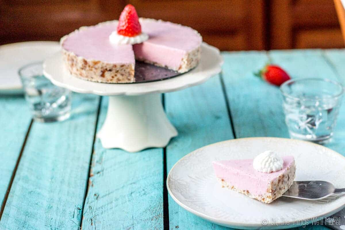 A paleo strawberrry cream pie on a cake stand with a slice missing. The slice is being places on a light beige plate with a spatula.