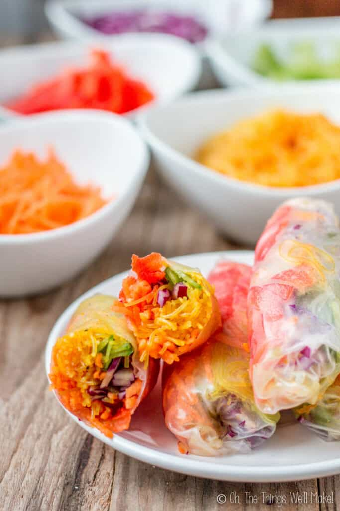 A plate full of spring rolls filled with colorful vegetables. One has been cut in half to show the filling.