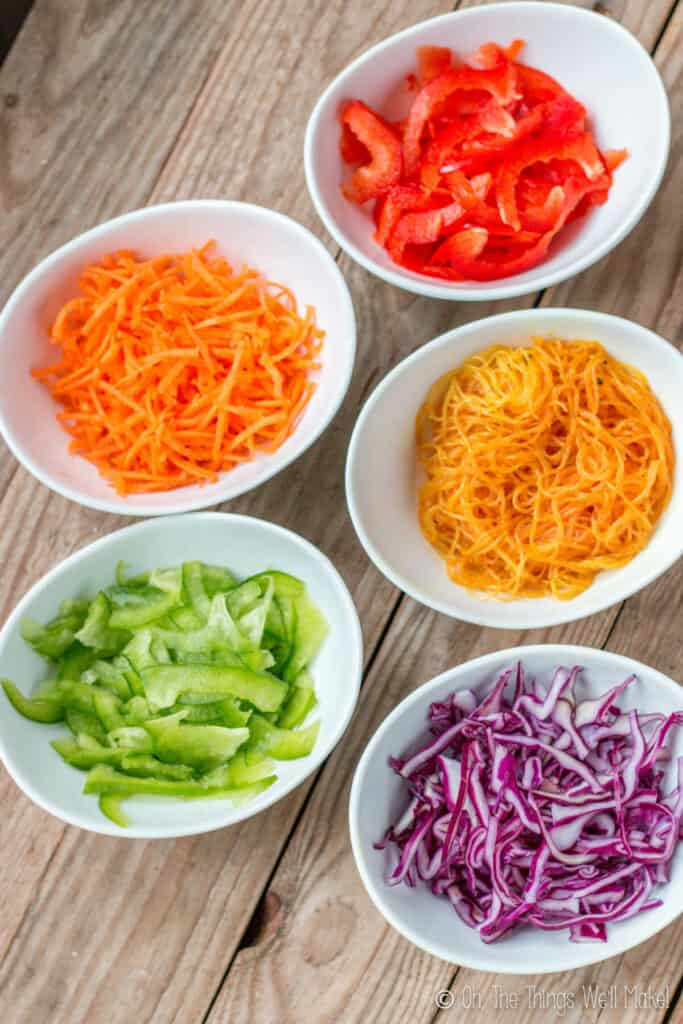 Overhead view of 5 bowls with a rainbow of fillings for spring rolls, including sliced red peppers, carrots, red cabbage, green peppers, and bean vermicelli turned yellow with curcuma.
