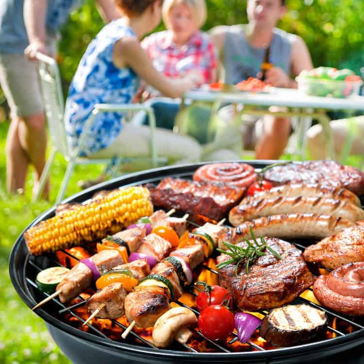 A barbecue grill filled with a variety of meats and veggies, in front of a family picnic
