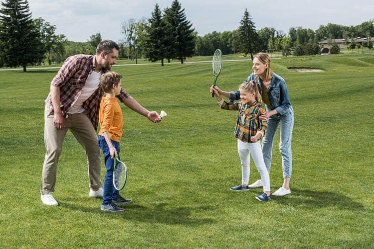 A family of four playing badminton