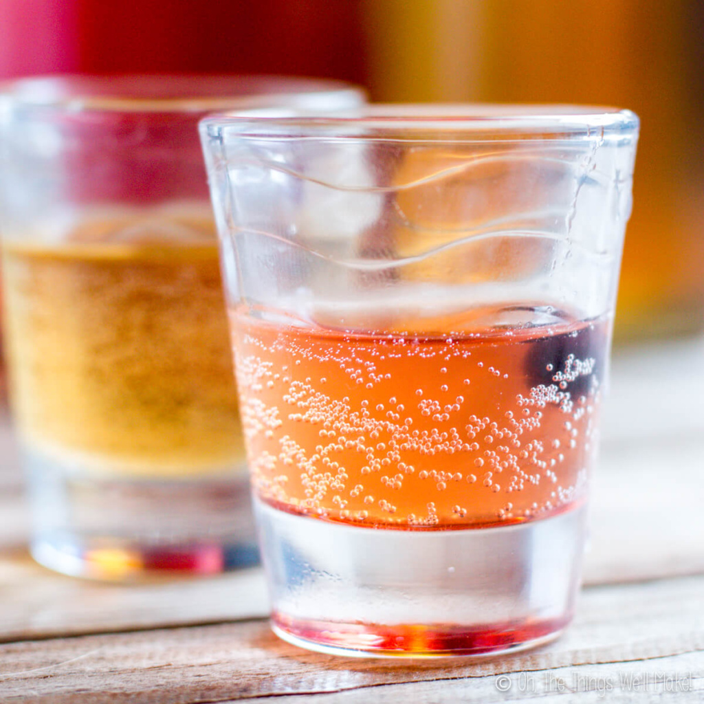 Two shot glasses filled with different flavors of kombucha closeup to show the bubbles.