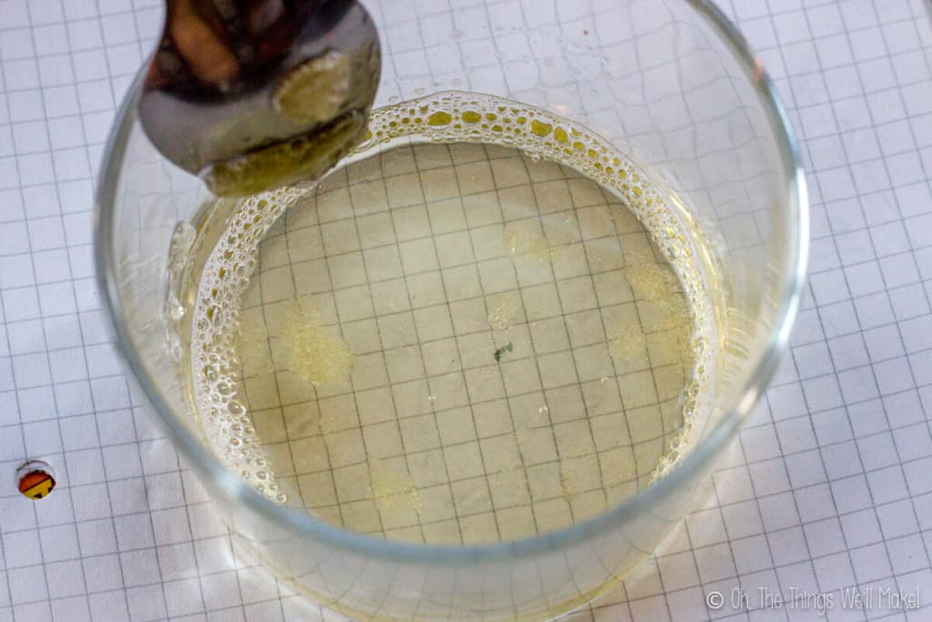 Liquid soap paste dissolved in a glass over a white paper