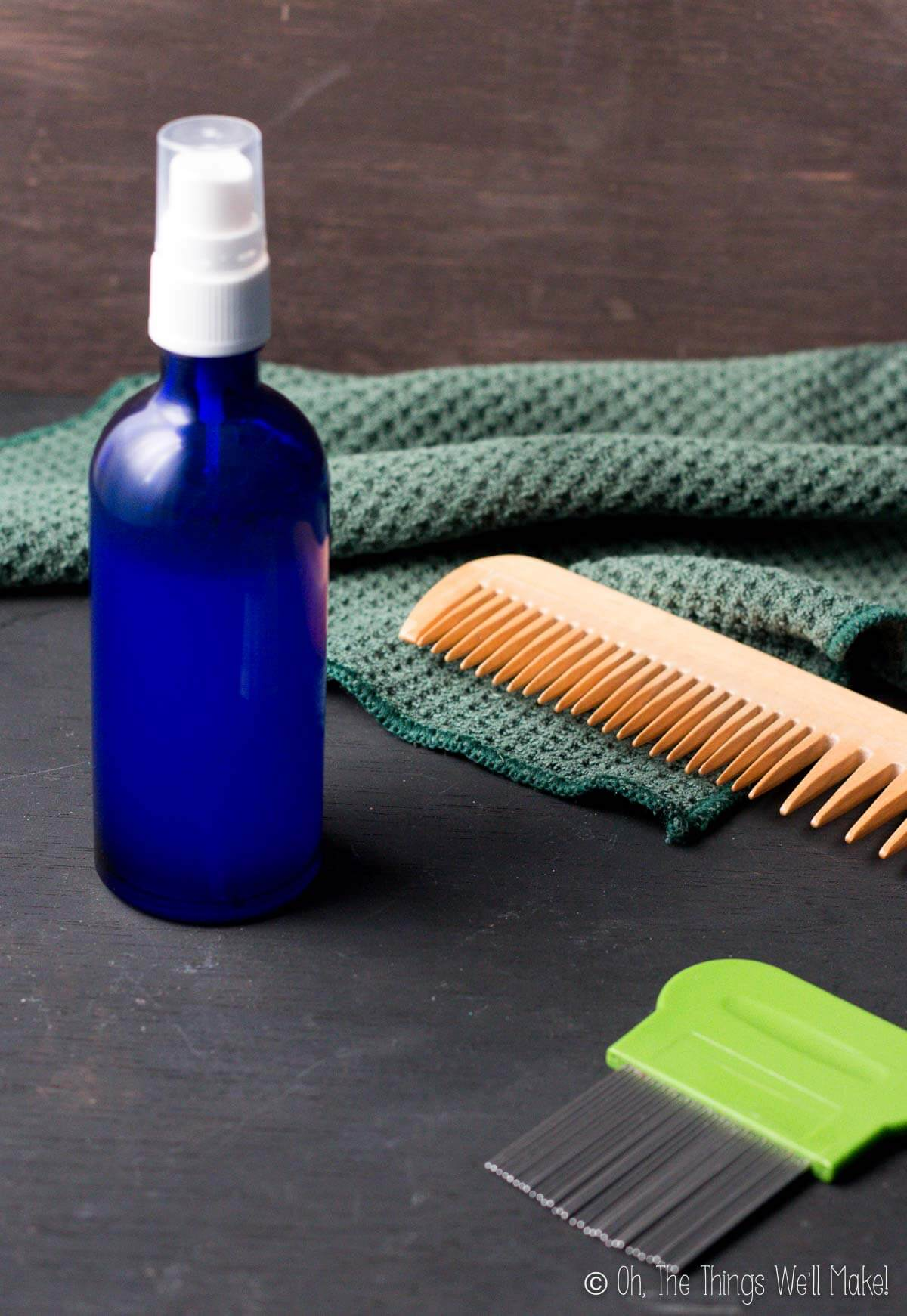 A blue bottle filled with a homemade lice repellent next to two combs and a washcloth