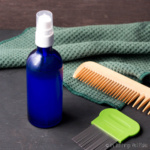 A bottle of a homemade lice spray with a nit comb and a wooden comb