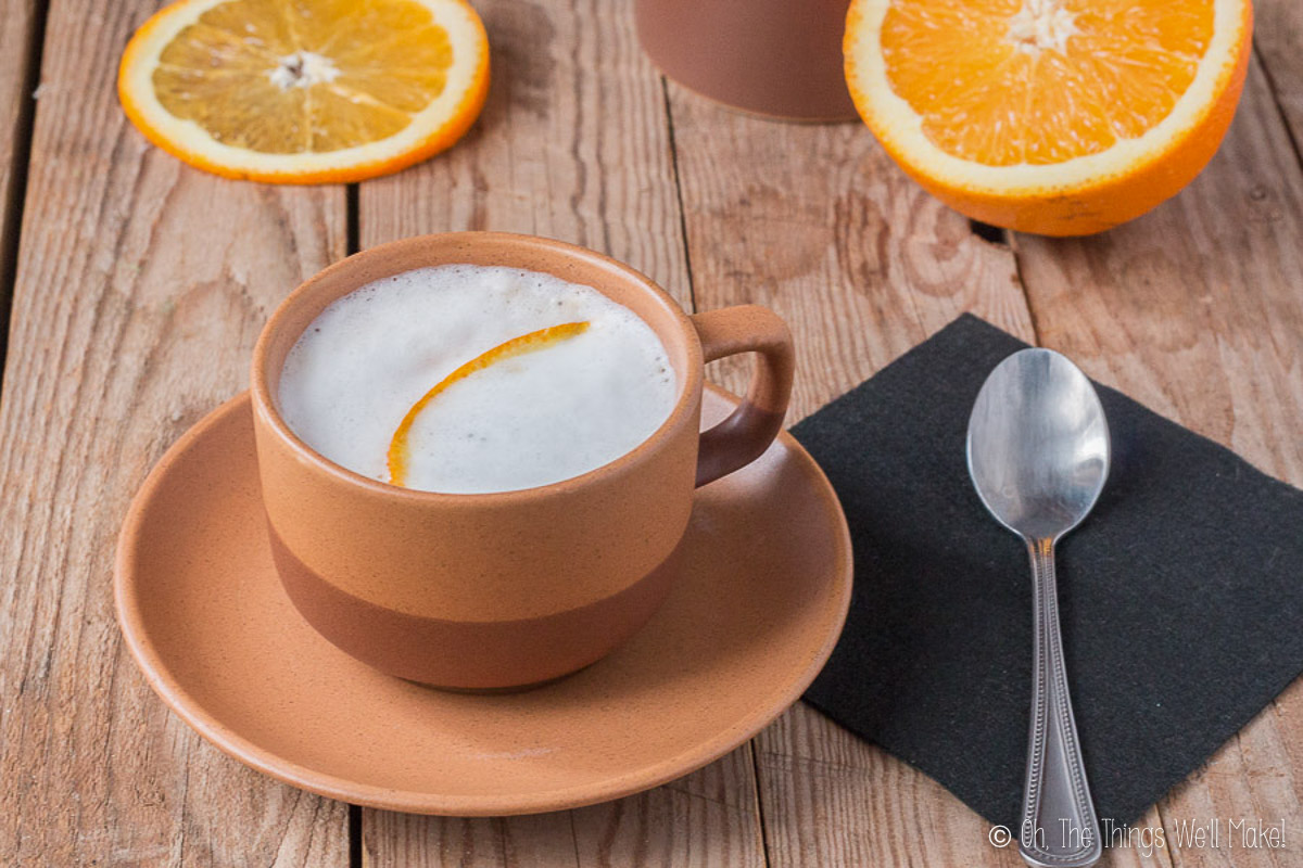 A cup of coffee with milk, garnished with orange zest