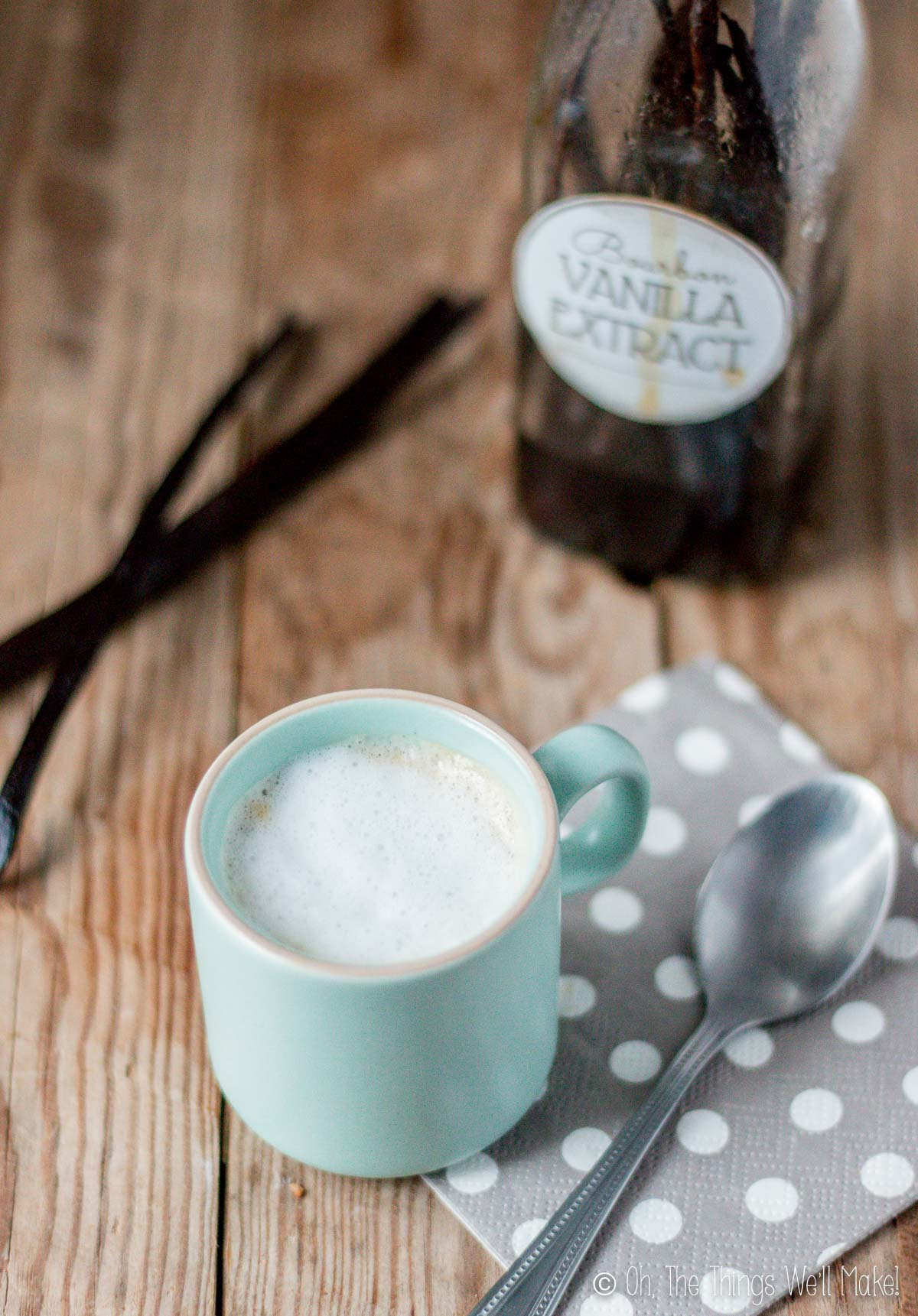 A cup of coffee with milk in front of a bottle of vanilla extract and some vanilla beans