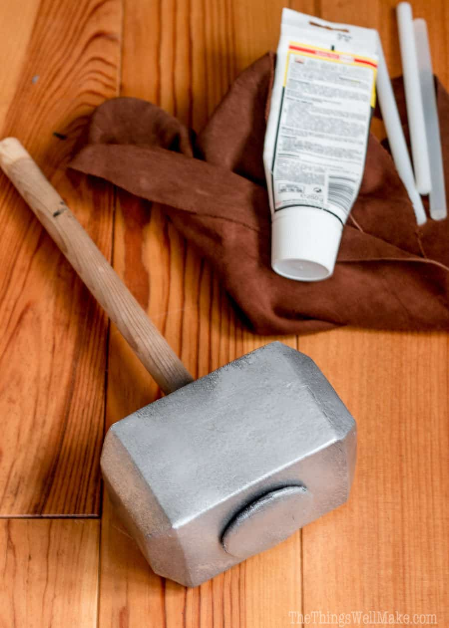Photo of painted Thor's hammer next to the suede fabric and glue which will be used for covering the dowel handle.
