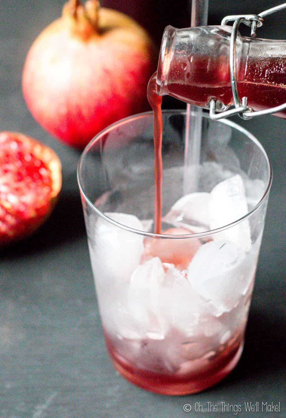 Pouring homemade grenadine into a glass with ice.