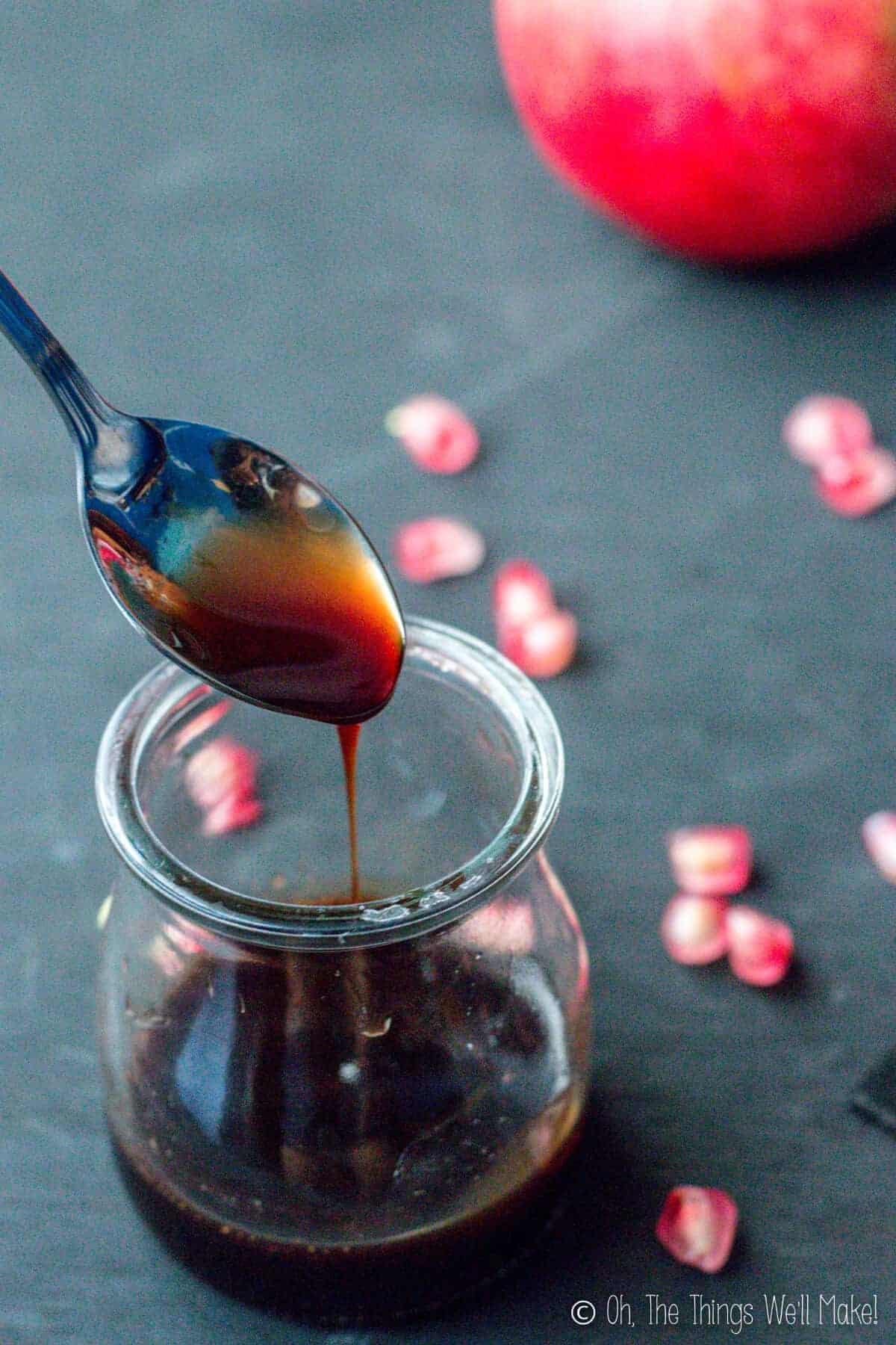 Homemade grenadine being spooned up and drizzled down into a small glass jar below.