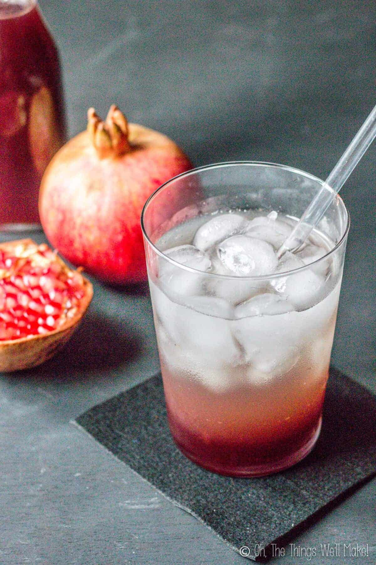 Closeup of a glass of soda and grenadine over ice in front of some pomegranates and a bottle of homemade grenadine.