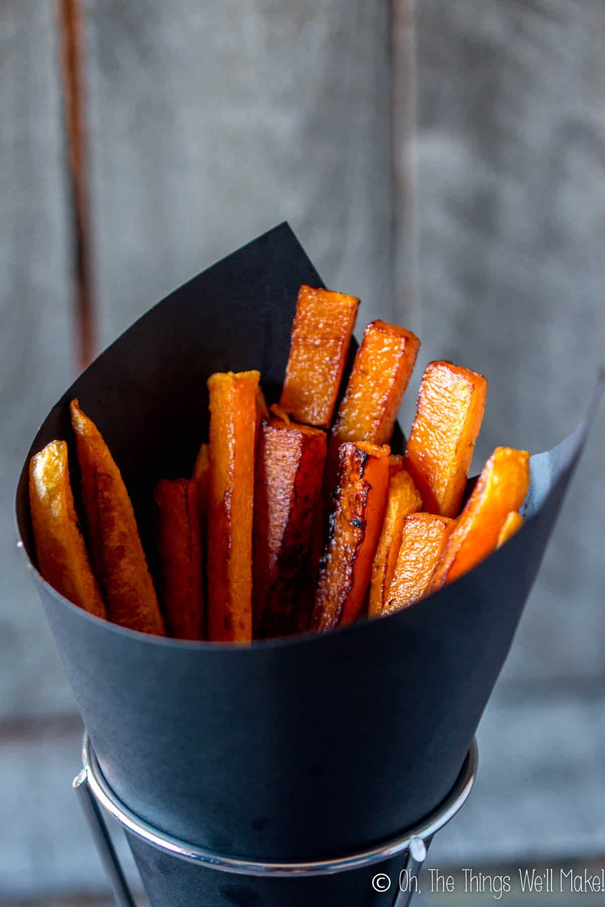 baked pumpkin fries in a black paper cone