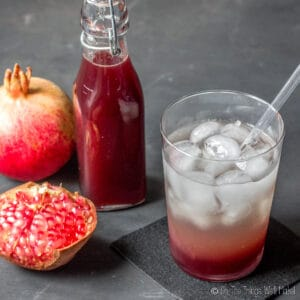 A closeup of a glass of soda and grenadine over ice in front of pomegranates and a bottle of homemade grenadine.
