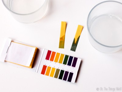 Closeup view of two pH test strips, one with a reading of around 9-10 and another at a pH 8-9.