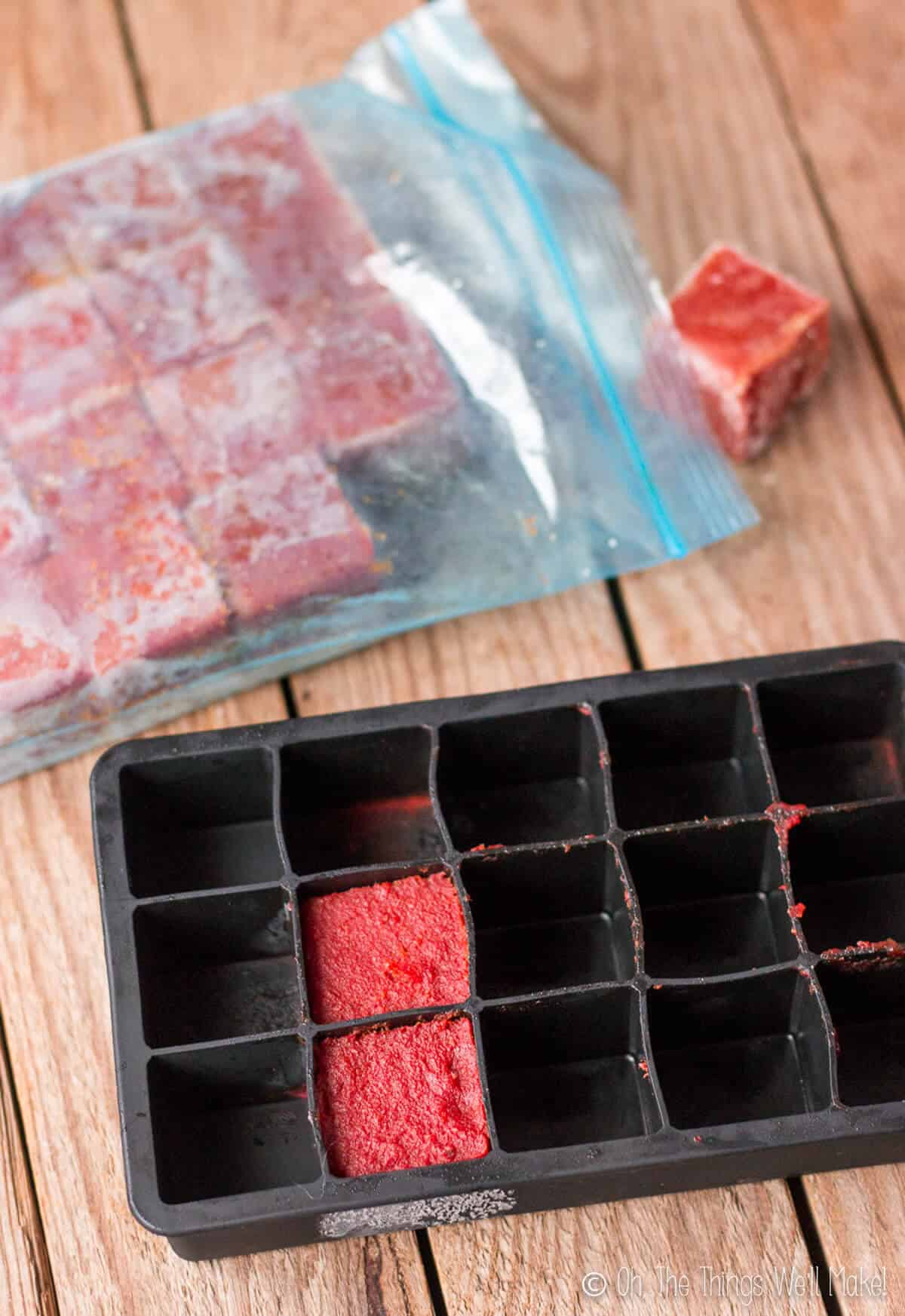 Overhead view of homemade tomato paste in ice cube trays for freezing and storing.