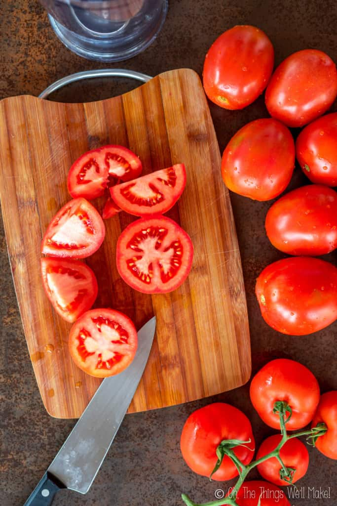 tomatoes being sliced on a cutting board
