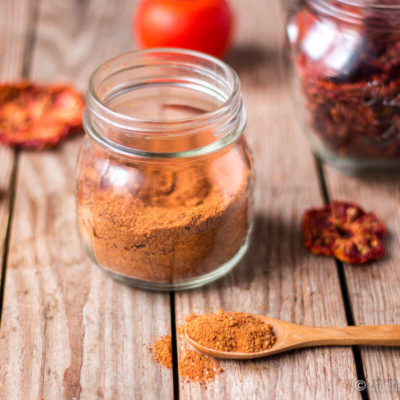 Tomato powder in a wooden spoon in front of a jar of tomato powder surrounded by dried tomato slices.