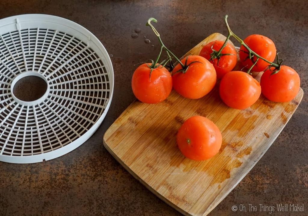 Overhead view of clean tomatoes on a bamboo cutting board