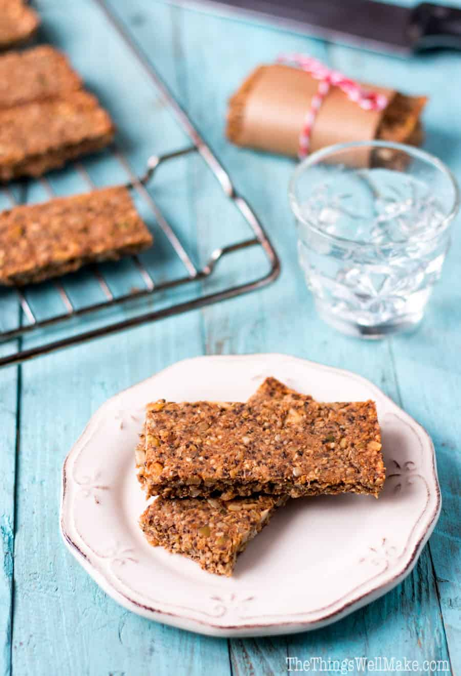 Homemade paleo granola bars on a plate in front of others on a cooling rack.
