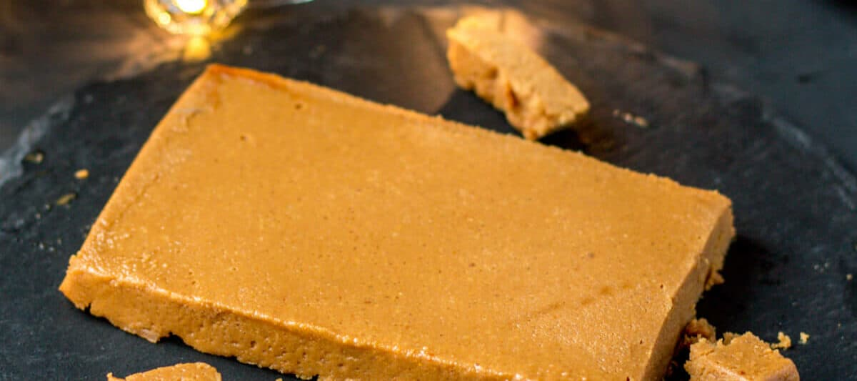 Homemade turrón de Jijona (soft almond nougat) on a black slate platter with small pieces cut from it.