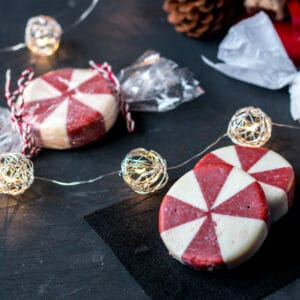 Round peppermint soaps that look like peppermint candies on a black background with Christmas lights.