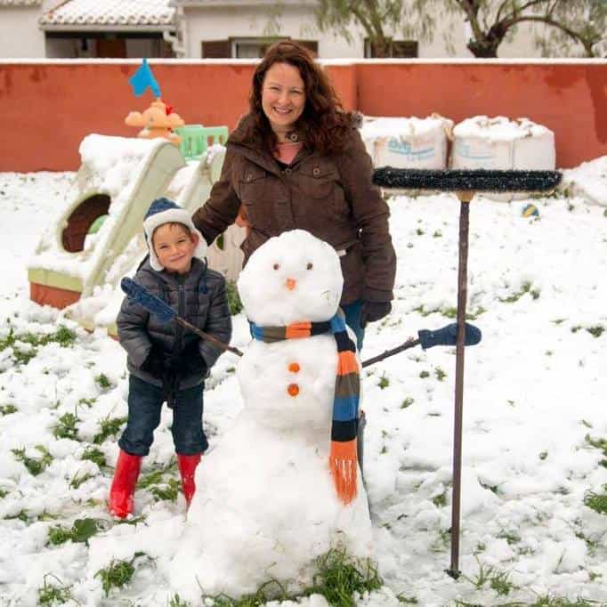 A boy and his mother standing behind a snowman