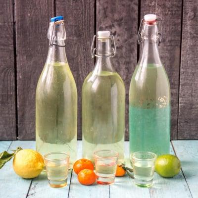 A bottle of homemade limoncello next to a bottle of homemade limecello and next to a bottle of mandarinecello