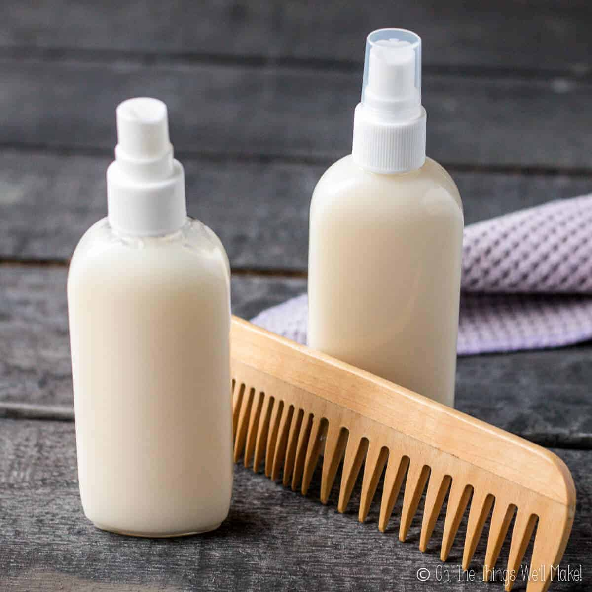 Two bottles of a homemade conditioner next to a wooden comb and a washcloth.