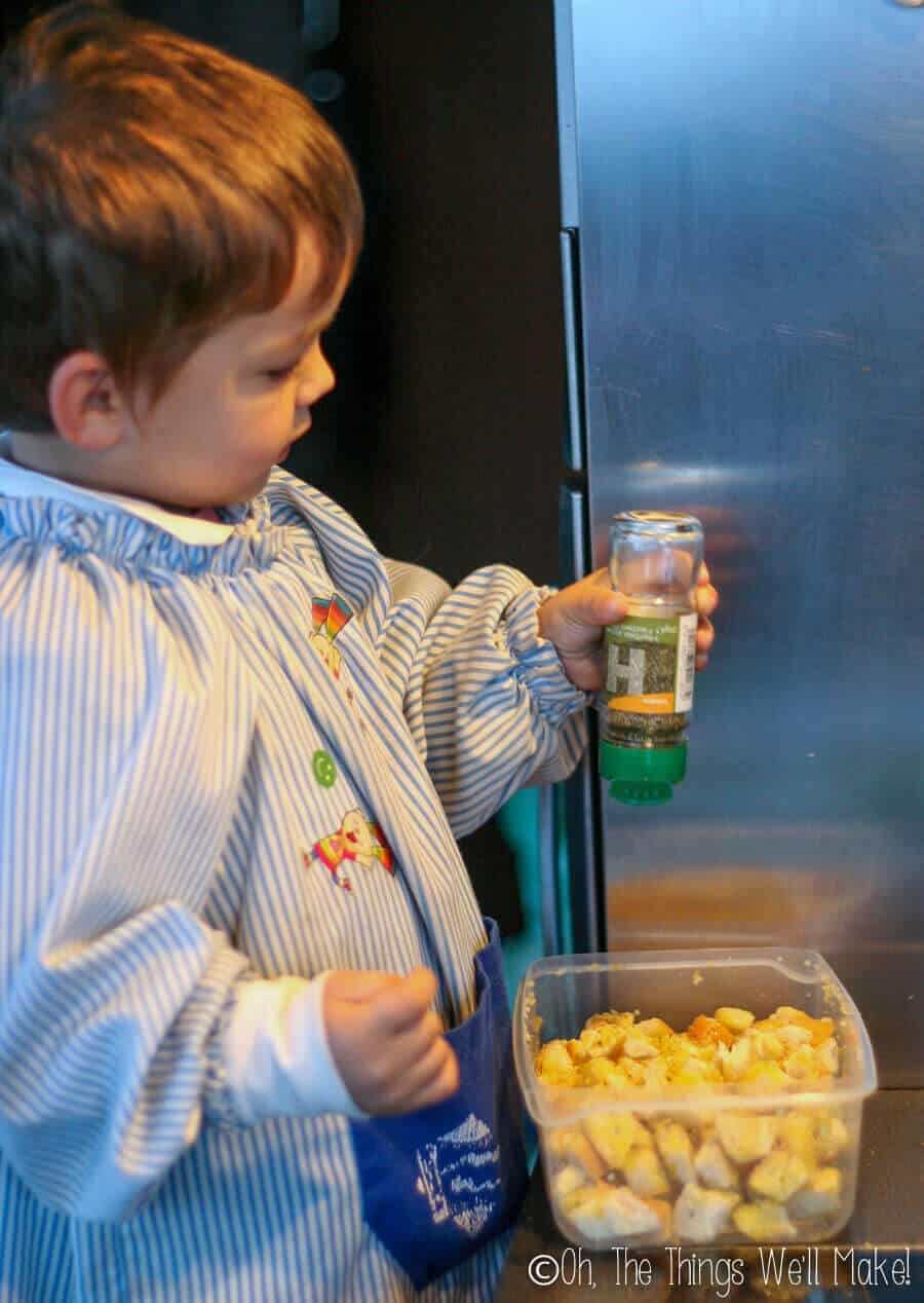 A little boy seasoning cubes of bread to make croutons