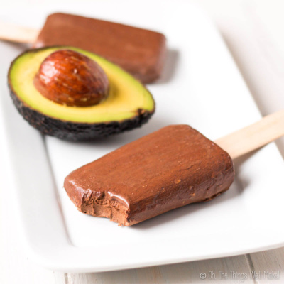 Two chocolate avocado pudding pops on a plate with half an avocado between them