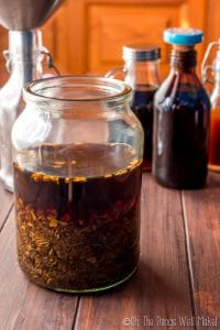 A jar filled with a mixture of bitter herbs and alcohol to make homemade bitters
