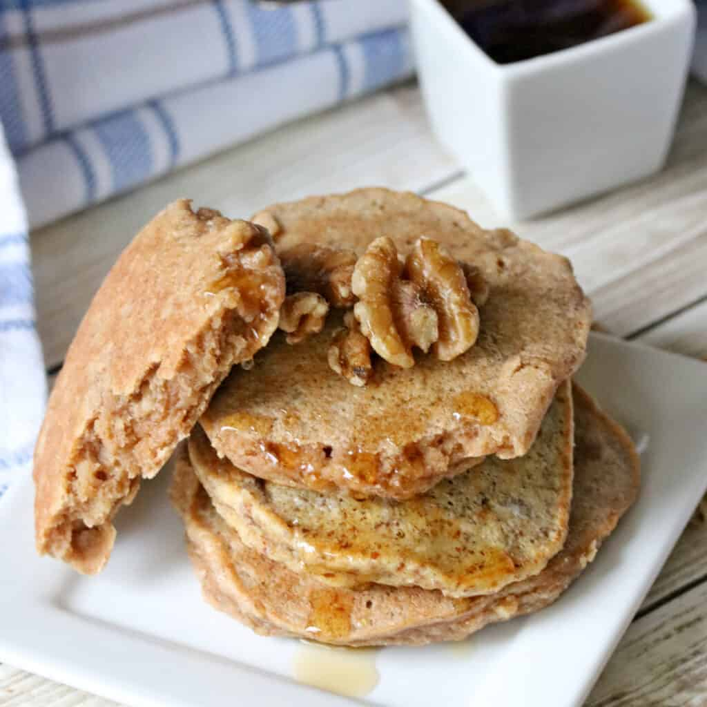 3 low carb walnut pancakes on a white plate with walnuts and maple syrup.