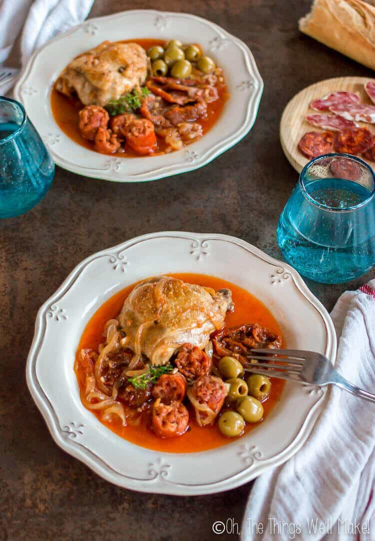 Basque chicken served on plates with chorizo, olives, sun dried tomatoes, and onions.