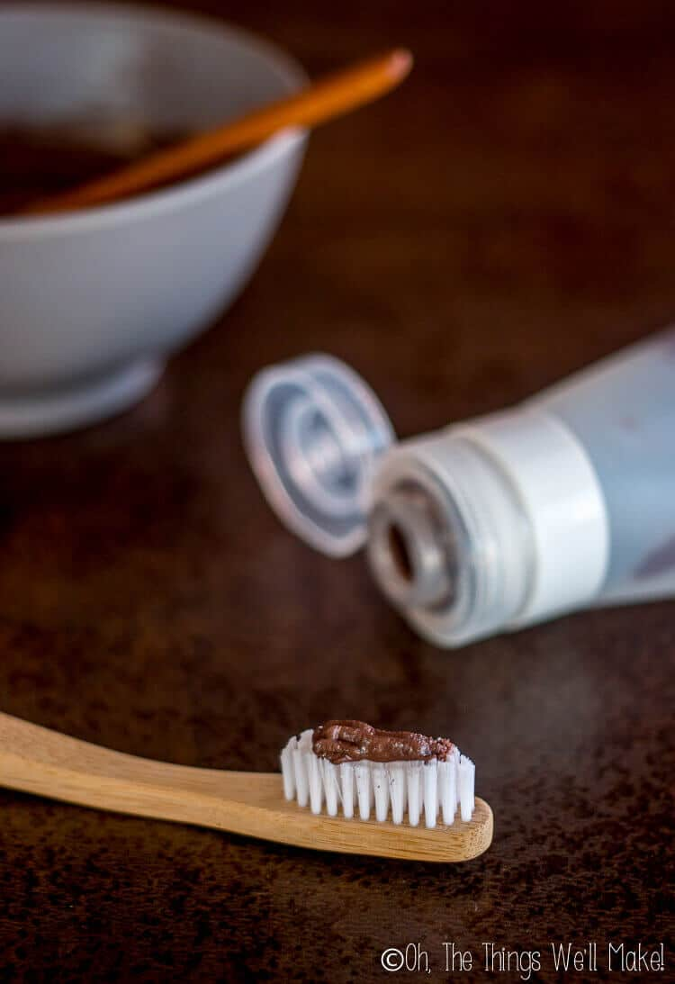 Homemade chocolate toothpaste on bamboo toothbrush below silicone travel tube of toothpaste.