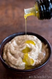 Drizzling olive oil on baba ganoush