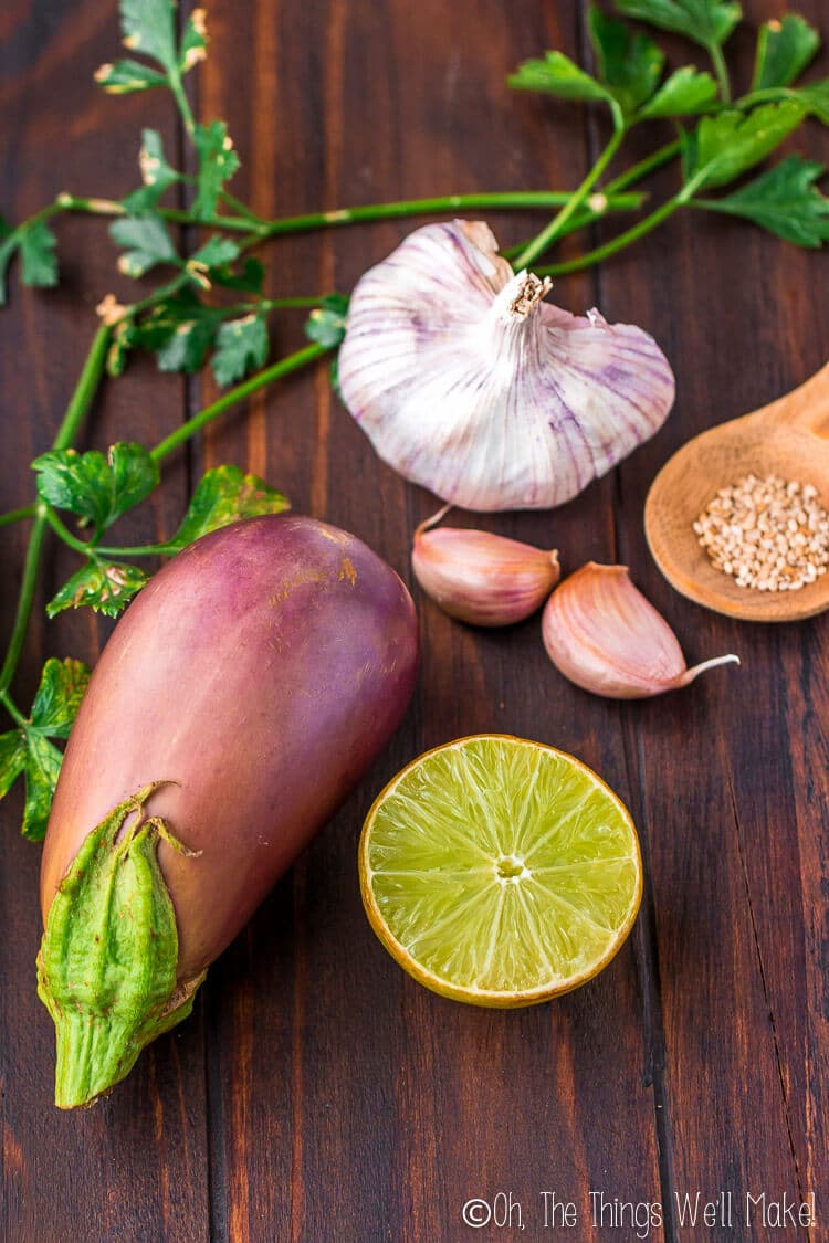 the ingredients for baba ganoush: eggplant, garlic, sesame seeds, and lemon or lime