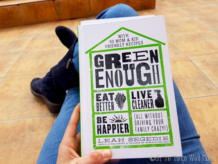Me holding the book Green Enough by Leah Segedie