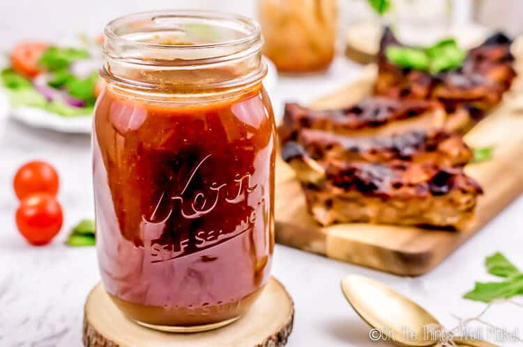 jar of homemade barbecue sauce in front of barbecue ribs