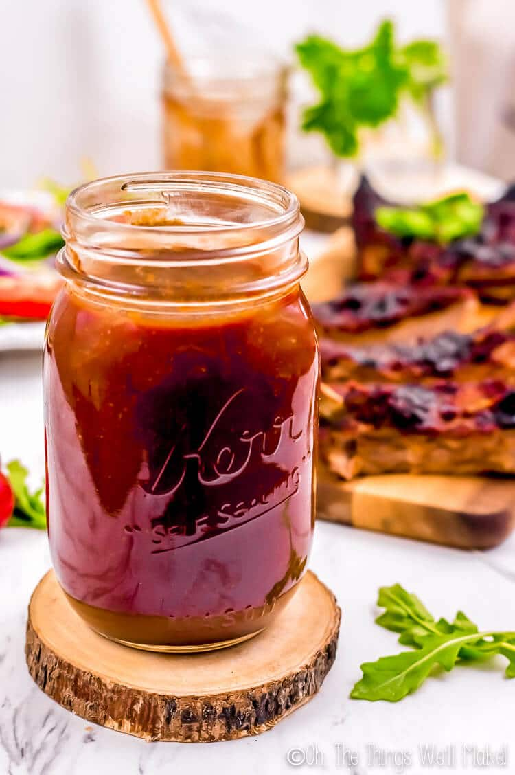 Easy homemade barbecue sauce in a jar in front of barbecue ribs