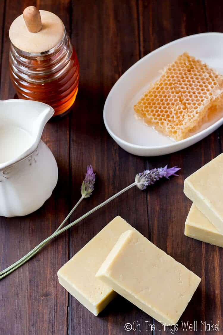 Bars of goat milk soap on a dark wood background next to a jar of honey, a honeycomb, some milk, and a couple of lavender flowers.