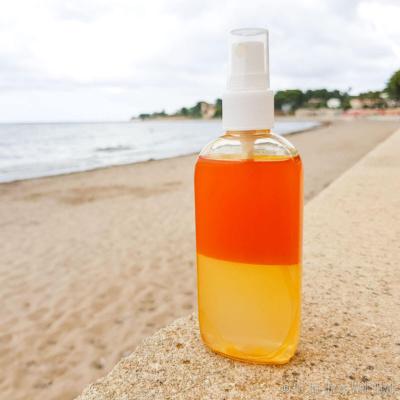 A bottle of homemade sea salt spray on a ledge by the beach.
