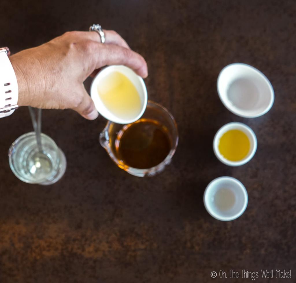 Pouring argan oil into a beaker with buriti oil